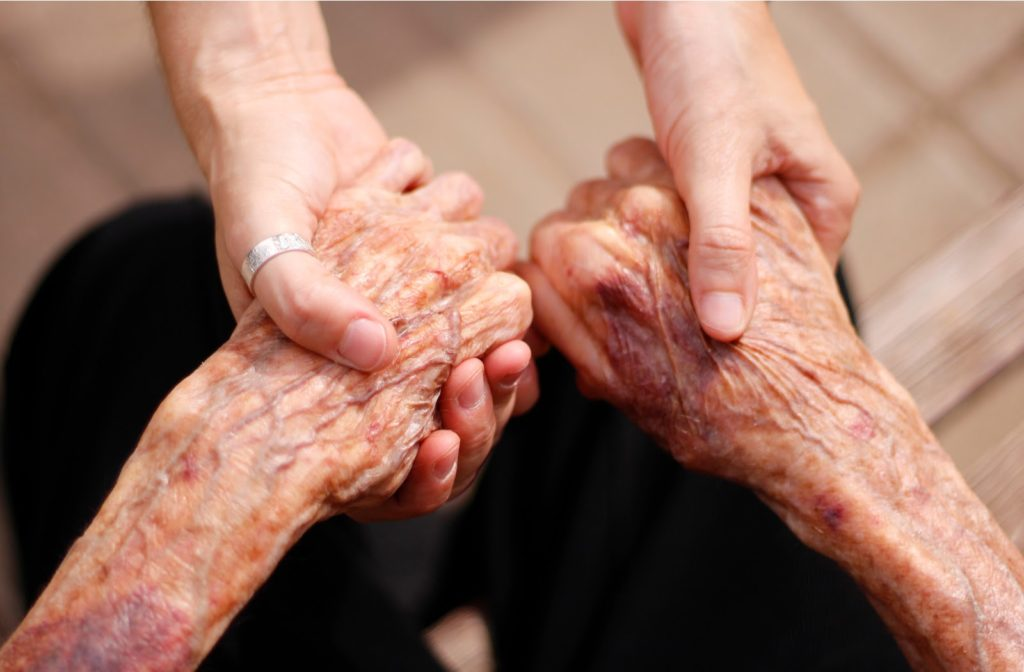 Elder lady and young woman holding hands