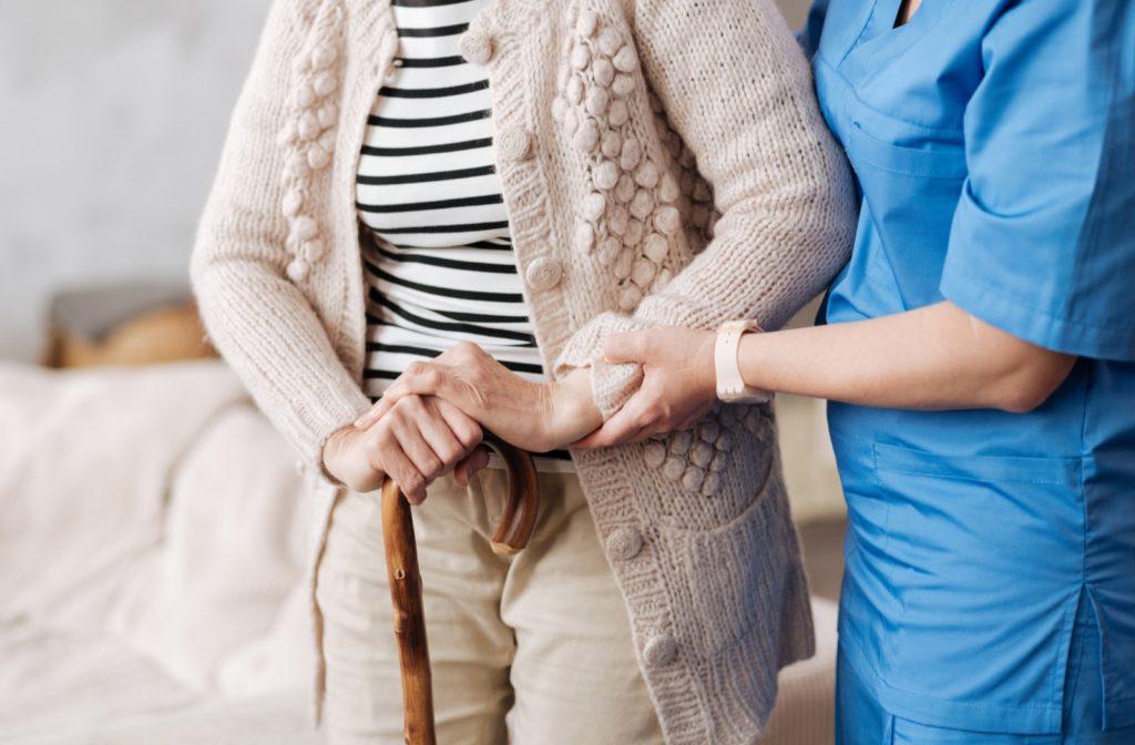 Nurse helping senior woman as they walk together.